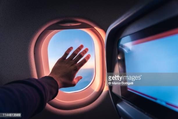 touching airplane window during flight at sunrise - inquadratura da un aereo foto e immagini stock