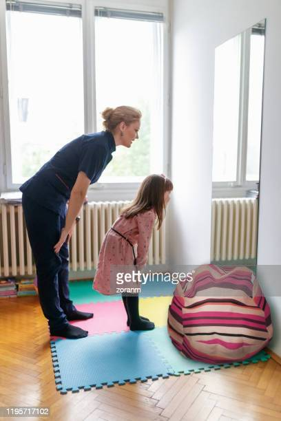 touching knees in body awareness exercise in front of the mirror - bend over woman stock pictures, royalty-free photos & images