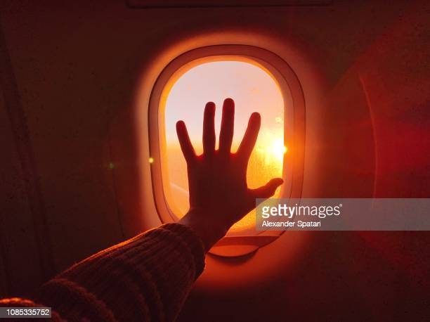 touching plane window while flying in the sky during sunset - admirer le paysage photos et images de collection