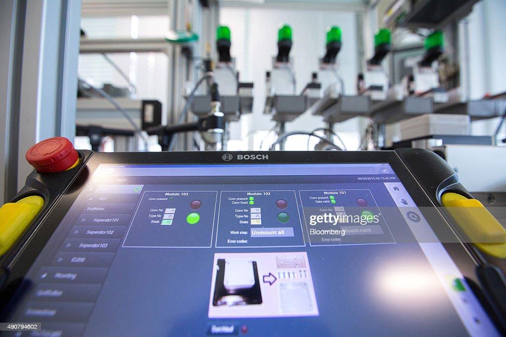 A touchscreen control panel sits beside a Bosch Rexroth