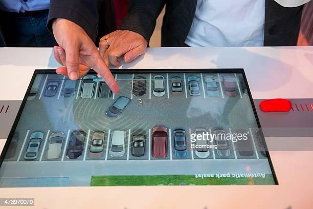 A touchscreen panel shows a demonstration of an automated car parking assistance app at Robert Bosch GmbH driverless technology press event in...