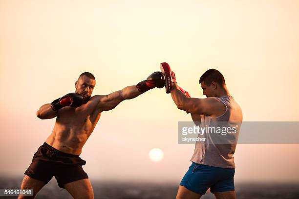 Tough boxer exercising at sunset with his personal trainer.