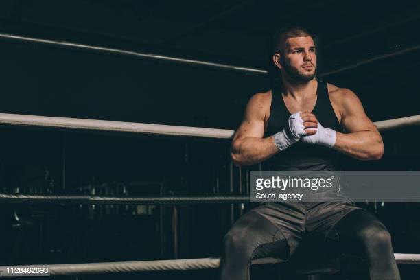 duro boxer seduto anello di boxe - sport da combattimento foto e immagini stock