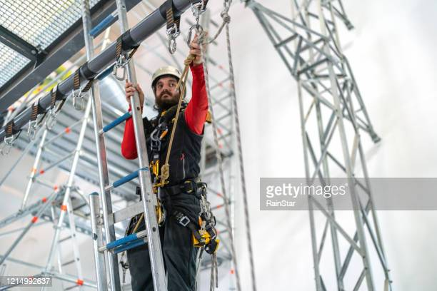 tough climb - safety harness stock pictures, royalty-free photos & images