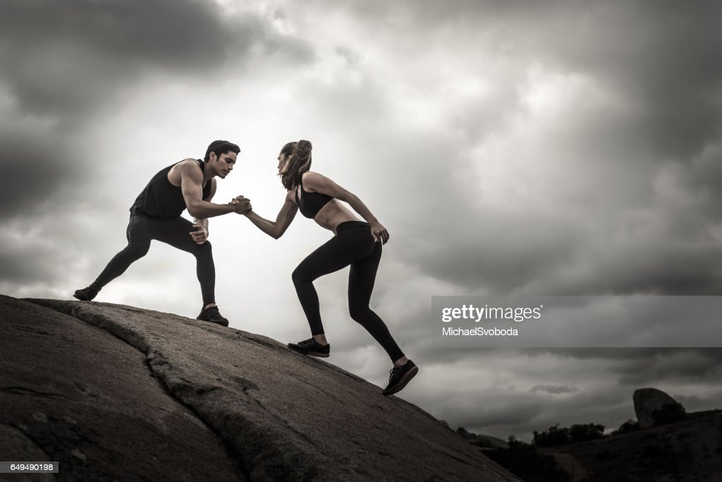 Helping Each Other: Tough Couple Helping Each Other Up Stock Photo