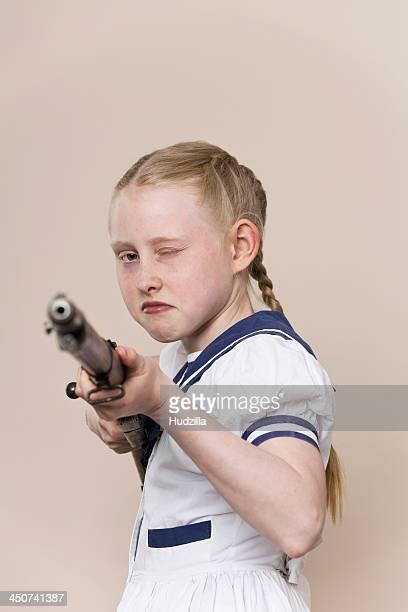 A tough girl wearing a sailor dress aiming a rifle at the camera