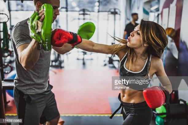 tough woman having kick boxing training with a coach. - mixed martial arts stock pictures, royalty-free photos & images