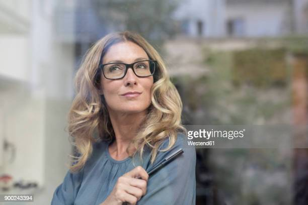 toughtful businesswoman behind windowpane - ideas stock-fotos und bilder