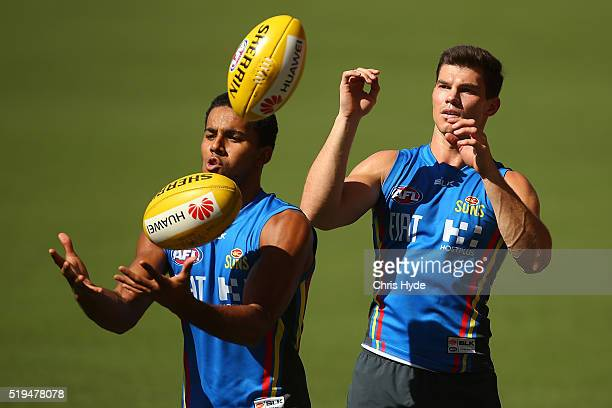 Touk Miller and Jaeger O'Meara handball during a Gold Coast Suns AFL training session at Metricon Stadium on April 7 2016 in Gold Coast Australia