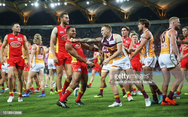 Touk Miller of the suns clashes with Mitch Robinson of the lions during the round 22 AFL match between the Gold Coast Suns and Brisbane Lions at...
