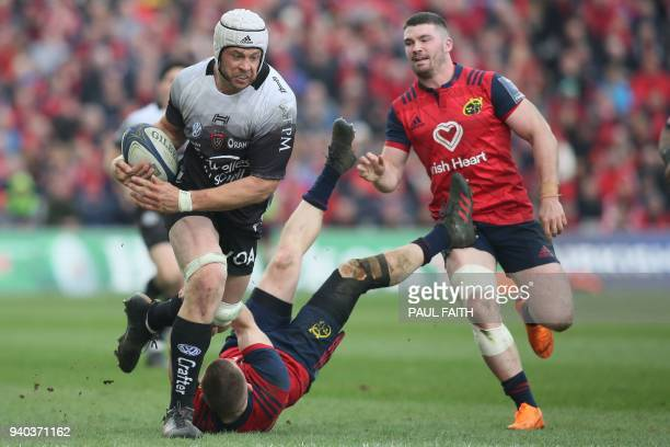 Toulon's English lock Dave Attwood runs through Munster's Irish wing Andrew Conway during the European Champions Cup quarter-final rugby union match...