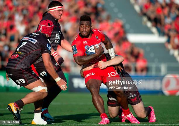 RC Toulon's Fijian winger Josua Tuisova vies with Llanelli's defenders during the European Champions Cup rugby union match between RC Toulon and...