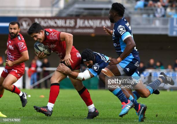 Toulon's French flyhalf Anthony Belleau is tackled by Montpellier's French center Alexandre Dumoulin during the French Top 14 rugby match between...