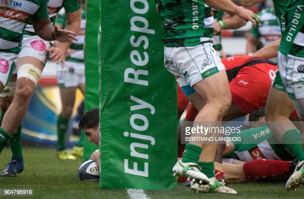 RC Toulon's French flyhalf Anthony Belleau scores a try despite Treviso's defenders during the Champions Cup rugby union match RC Toulon vs Benetton...