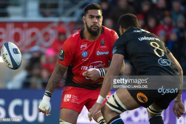 RC Toulon's French lock Romain Taofifenua passes the ball as Bath's number 8 Taulupe Faletau looks on during the Champions Cup rugby union match RC...