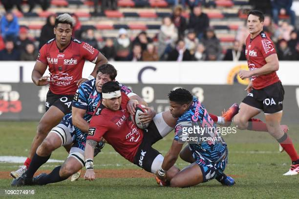 Toulon's French number 8 Raphael Lakafia is tackled by Stade Francais' French centre Jonathan Danty and Stade Francais' South African flanker Willem...
