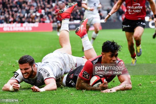 Toulon's New Zealander center Malakai Fekitoa dives to score next to Toulouse's French center Lucas Tauzin during their Top 14 rugby union match...