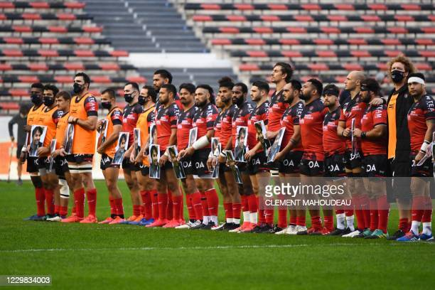 Toulon's players pay their respect in tribute to late French player Christophe Dominici at the start of the French Top14 rugby union match between...
