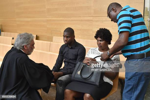 Toulouse football player Odsonne Edouard speaks with his lawyer Pierre Le bonjour as his parents look on prior to his hearing for 'armsbased...
