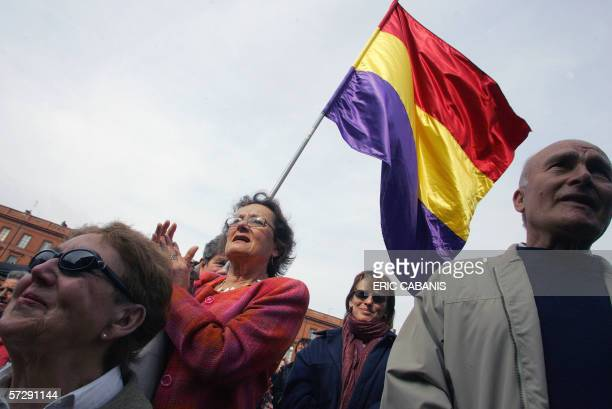 People listen to former soldiers' speeches as a Spanish second republic flag flutters during the 75th anniversary commemoration of the second Spanish...