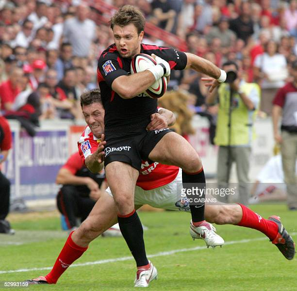 Stade Toulousain's winger Vincent Clerc is tackled by Auch's winger Julien Kinane during their French Top 16 rugby union match, 28 May 2005 at the...