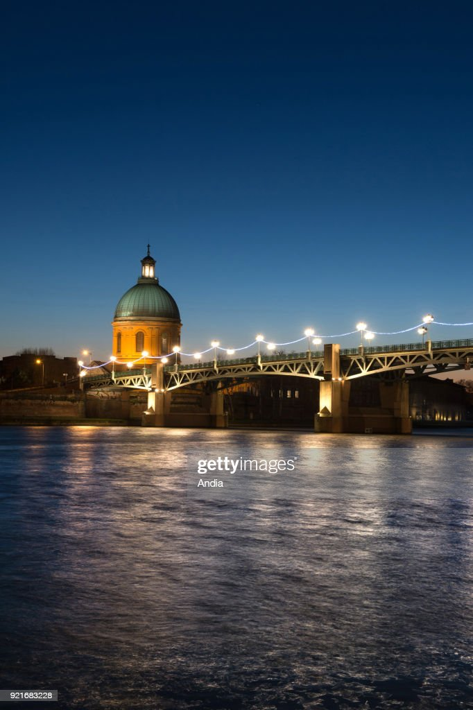night view of St Peter's Bridge (French 'pont Saint-Pierre') across the Garonne river and the dome of the 'hopital de la Grave' hospital.