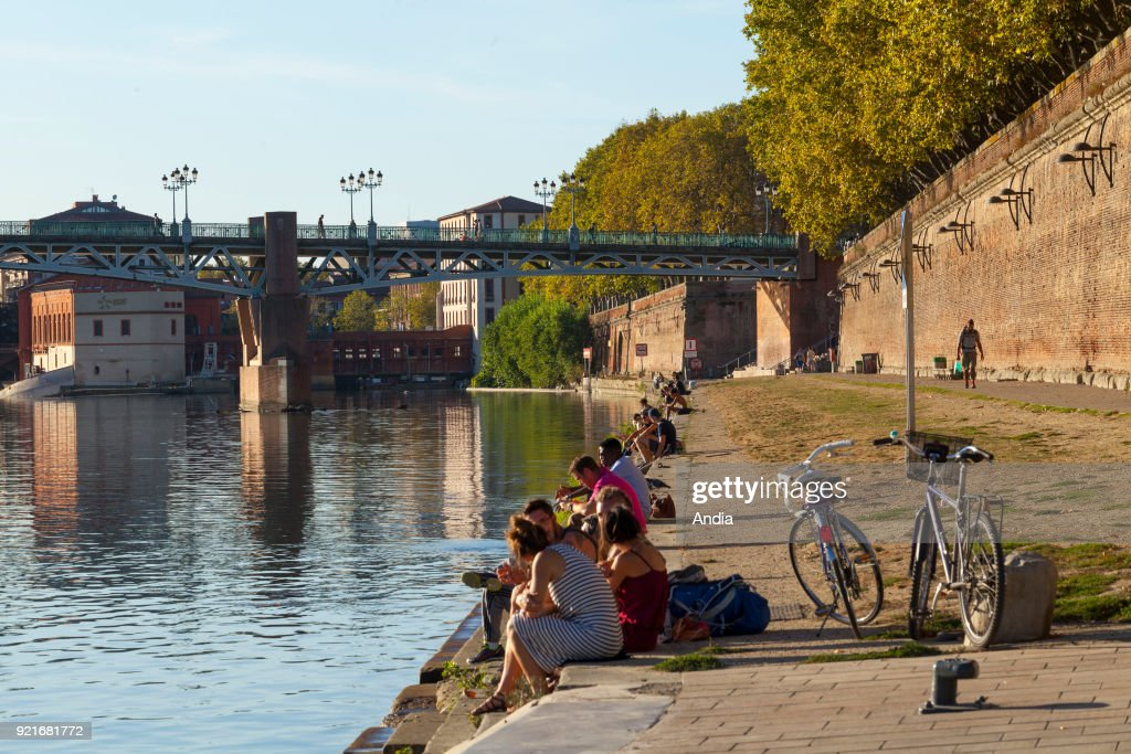 walk and relaxation along the banks of the River Garonne in summer, viewed from the 'quai de la Daurade' quay. People sitting by the river, bikes and 'Pont Saint-Pierre' bridge in the background.
