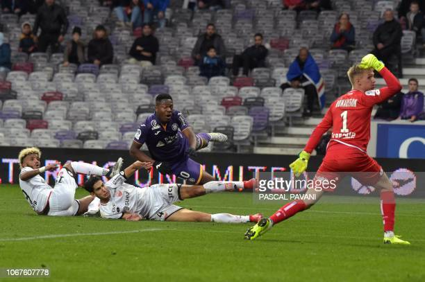 Toulouse's Belgian forward Aaron Leya Iseka vies with Dijon's Moroccan defender Nayef Aguerd Dijon's French defender Valentin Rosier and Dijon's...