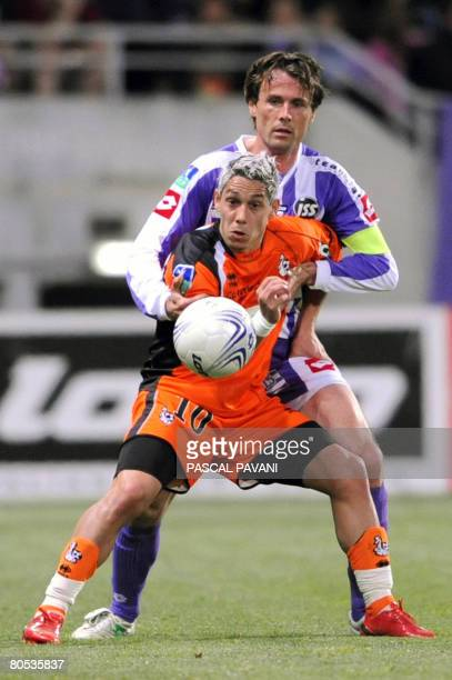 Toulouse's defender Dominique Arribage vies with Lorient's forward Nicolas Marin during the French L1 football match at the Stadium in Toulouse on...