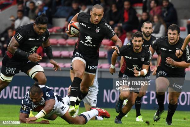 Toulouse's French centre Gael Fickou runs with the ball past Agen's French flanker Yoan Tanga Mangene during the French Top 14 rugby union match...