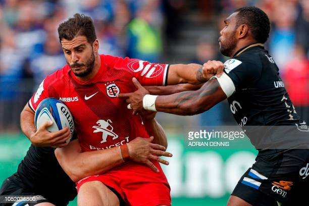 Toulouse's French centre Sofiane Guitoune is tackled by Bath's English lock Dave Attwood and Bath's English wing Semesa Rokoduguni during the...
