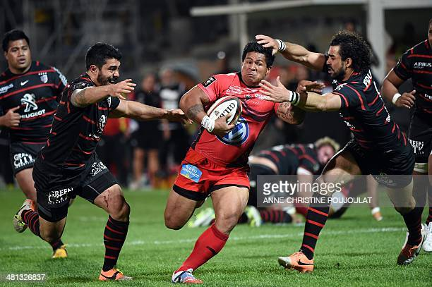 Toulouse's French centre Yann David and teammate French winger Yoann Huget try to stop RCToulon's Samoan winger David Smith during the French Top 14...