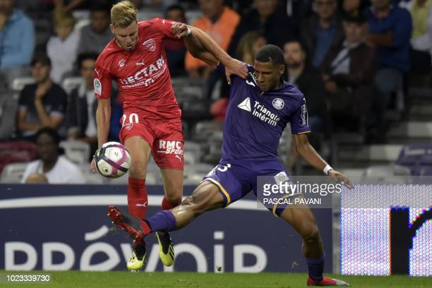 Toulouse's French defender JeanClair Todibo vies for the ball with Nimes's French forward Renaud Ripart during the French L1 football match between...