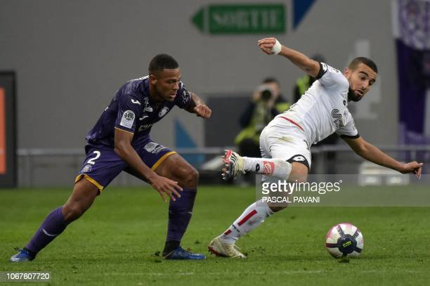 Toulouse's French defender Kelvin Amian vies with Dijon's FrenchTunisian midfielder Naim Sliti during the French L1 football match between Toulouse...