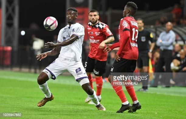 Toulouse's French forward Yaya Sanogo controls the ball past Guingamp's Congolese forward Yeni Ngbakoto and Guingamp's Portuguese defender Rebocho...