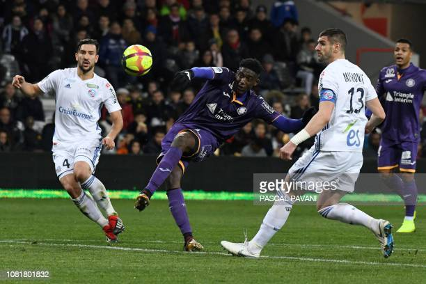 Toulouse's French forward Yaya Sanogo vies with Strasbourg's French midfielder Pablo Martinez and Strasbourg's Serbian defender Stefan Mitrovic...