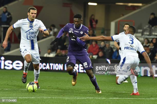 Toulouse's French forward Yaya Sanogo vies with Troyes' Brazil defender Gabriel Dos Santos Magalhaes and Troyes's Venezuela defender Oxwaldo...