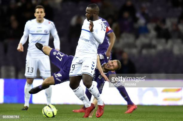 Toulouse's French midfielder Alexis Blin fallas next to Strasbourg's French forward Stephane Bahoken during the French L1 football match between...