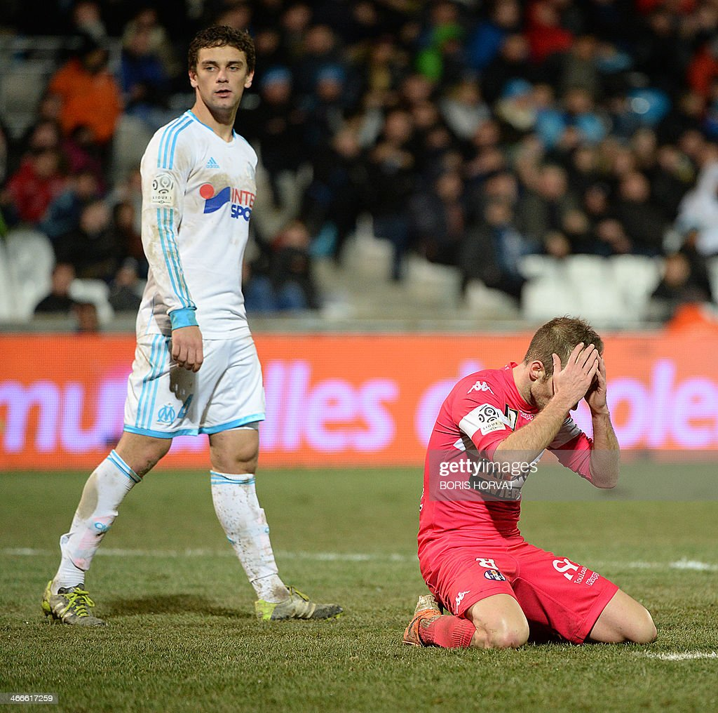 Toulouse's French midfielder Etienne Didot (R) reacts after missing a chance to score as Marseille's Brazilian defender Lucas Mendes looks on during the French L1 football match Olympique de Marseille vs Toulouse at the Velodrome stadium in Marseille, on February 2, 2014.