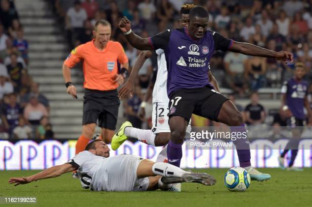 Toulouse's French midfielder JeanVictor Makengo vies with Dijon's French midfielder Romain Amalfitano during the French L1 football match between...