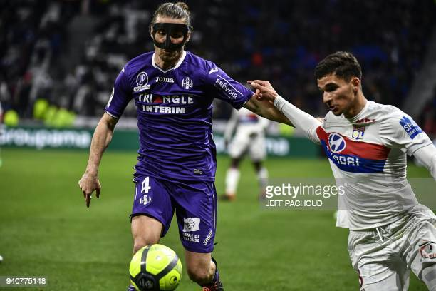 Toulouse's French midfielder Yannick Cahuzac fights for the ball with Lyon's forward Houssem Aouar during the French L1 football match Olympique...
