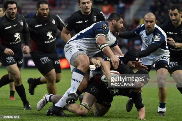 Toulouse's French number eight François Cros is tackled by Montpellier's French number eight Alexandre Dumoulin and Montpellier's Georgian prop Davit...