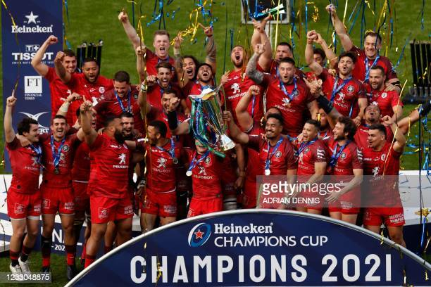 Toulouse's French scrum-half Antoine Dupont and teammates lift the trophy and celebrate victory after the European Champions Cup final rugby union...