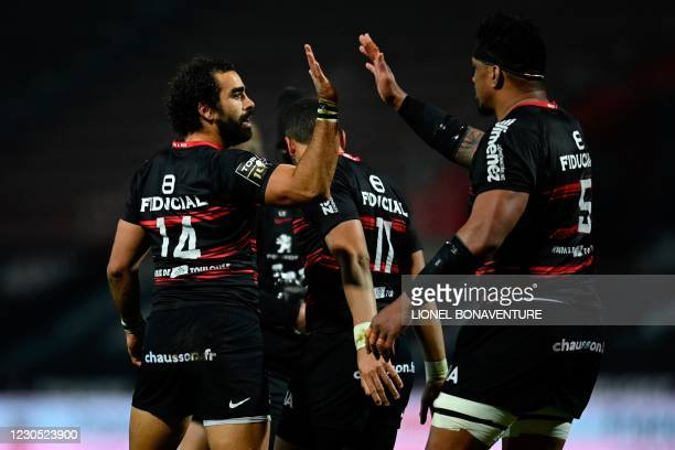 Toulouse's French wing Yoann Huget celebrates with teammates after he scores a try during the French Top 14 rugby union match between Toulouse and...