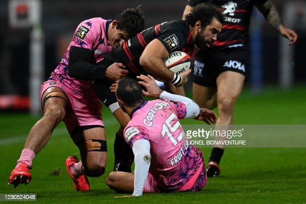 Toulouse's French wing Yoann Huget is tackled by Stade Français' French full back Kylan Hamdaoui and Stade Français' Argentinian flanker Paul Matera...