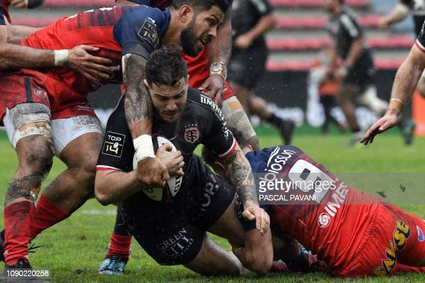 Toulouse's French winger Sofiane Guitoune vies with Grenoble's French scrum-half Theo Nanette and Grenoble's Tongan centre Alaska Taufa during the...