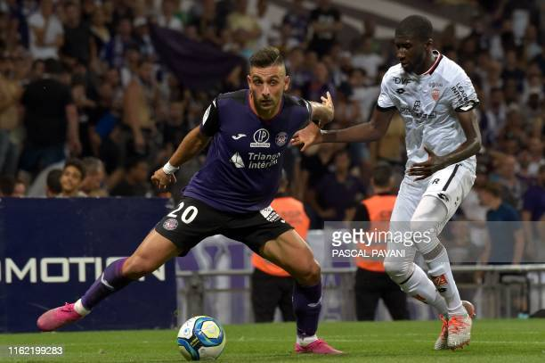 Toulouse's Greek forward Efthymios Koulouris vies with Dijon's French defender Senou Coulibaly during the French L1 football match between Toulouse...