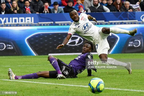 Toulouse's Guinean defender Issiaga Sylla fights for the ball with Lyon's Ivorian forward Maxwell Gnaly Cornet during the French L1 football match...