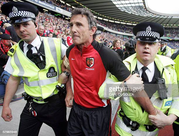 Toulouse's head coach Guy Noves is led away by police after his team beat Stade Francais in a Heineken Cup Final match at Murrayfields stadium...