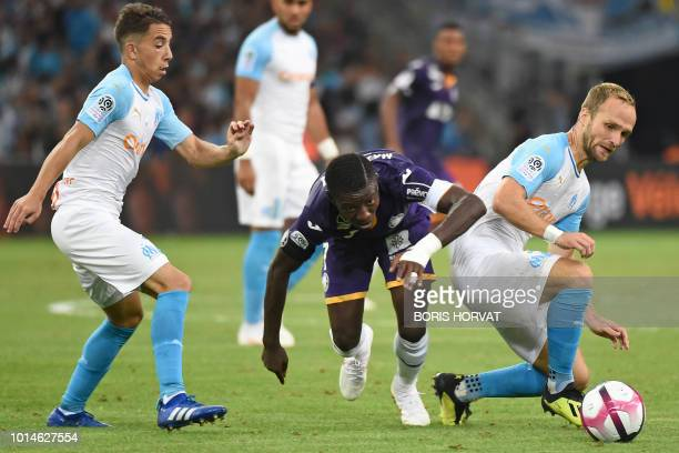 Toulouse's Ivorian forward MaxAlain Gradel vies for the ball with Olympique de Marseille's French midfielder Maxime Lopez and Olympique de...